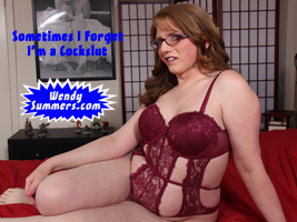Wendy lounging on the bed in a maroon lace teddy